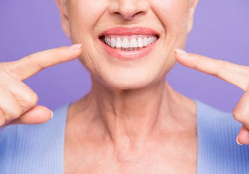 Concept of having strong healthy straight white perfect teeth at old age. Cropped portrait of beaming smile female pensioner pointing on her teeth, isolated over violet background